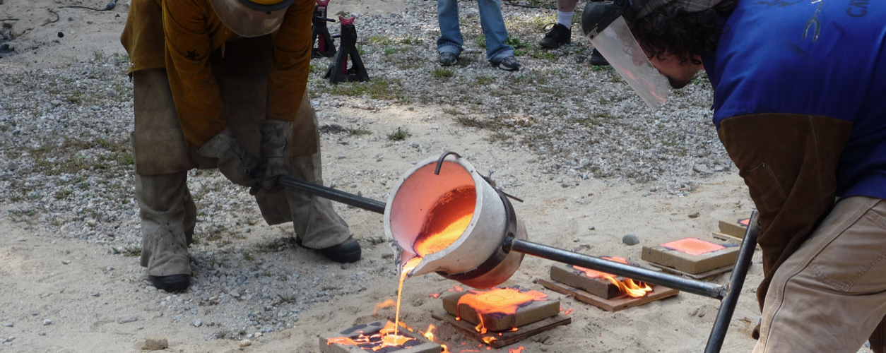 Two men pouring molten iron into molds.